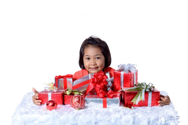 Feliz niño asiático con regalos de navidad.