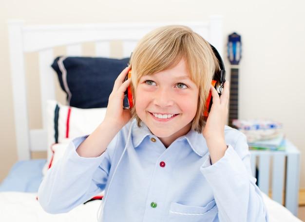 Feliz niño escucha música sentada en la cama