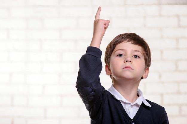 Feliz niño de escuela primaria apunta con su dedo.