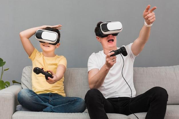 Feliz niño y hombre jugando videojuegos con casco de realidad virtual