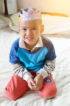 Feliz niño jugando con ser el rey, niño pequeño asiático disfrutar de viajes, viajes y concepto de recreación