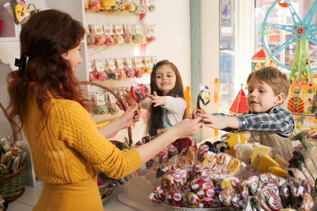 Feliz niño y niña comprando dulces en la tienda