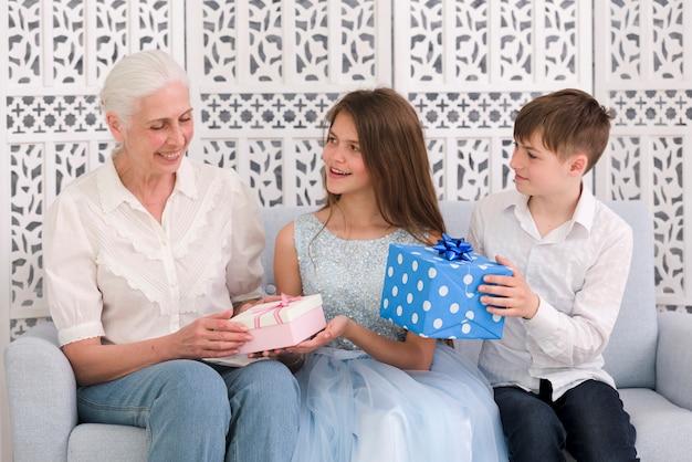 Feliz niño y niña dando cajas de regalo a su abuela en la fiesta de cumpleaños