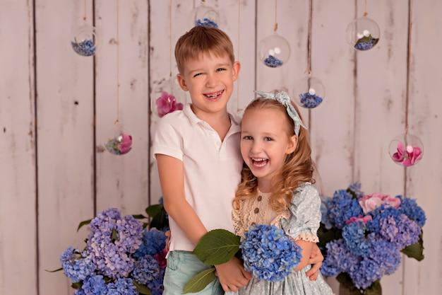 Feliz niño y niña en estudio sobre fondo blanco con flores de hortensias rosas y azules