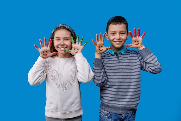 Feliz niño y niña con manos de colores en un azul
