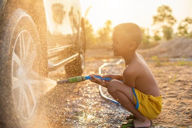 Feliz niño pequeño asiático jugando agua de manguera