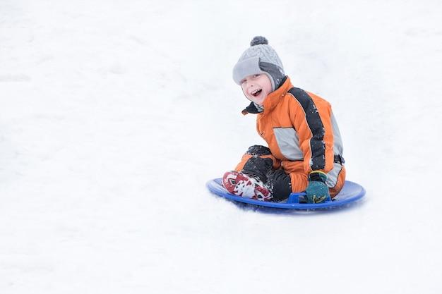 Feliz niño pequeño riendo se desliza cuesta abajo en el plato de nieve