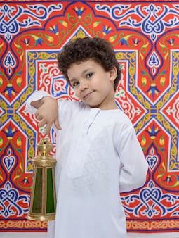 Feliz niño sonriente con linterna celebrando el ramadán