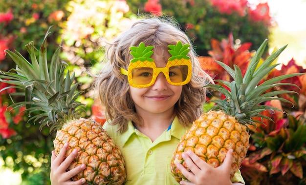 Feliz niño sonriente tiene piña en manos, niños y frutas tropicales.