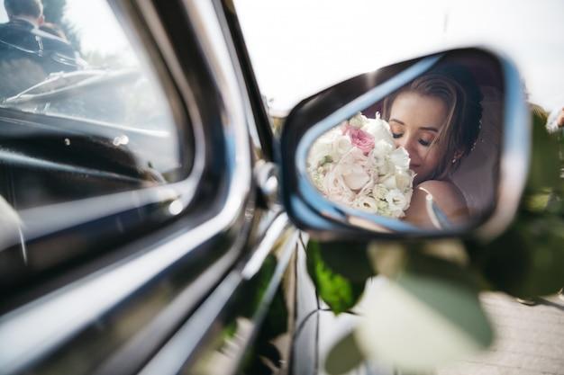 Feliz novia huele flores en el coche