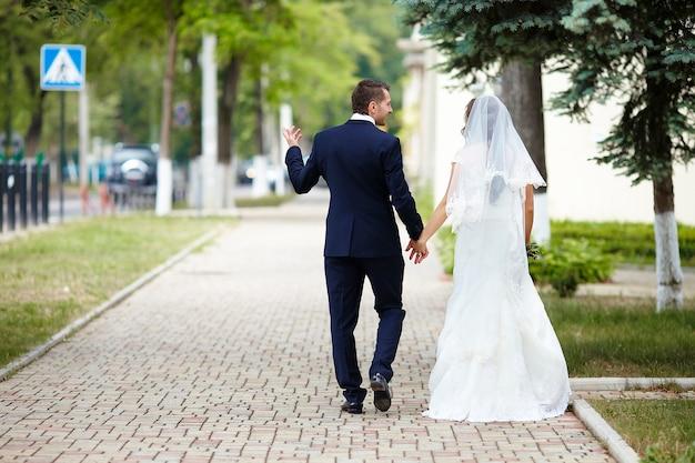 Feliz novia y el novio en una calle de la ciudad. pareja de boda.