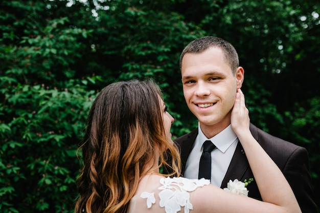 Feliz novia y el novio casándose en el bosque verde.