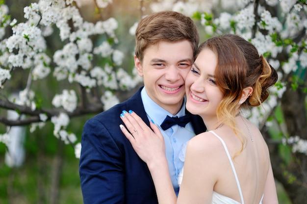 Feliz novia y el novio en un floreciente jardín de primavera