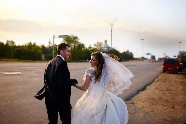 Feliz novia y el novio fuera de la ciudad en la carretera. pareja de boda.