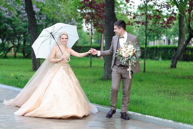 Feliz novia y el novio con un paraguas blanco bajo la lluvia, en verano en el parque. boda al aire libre.