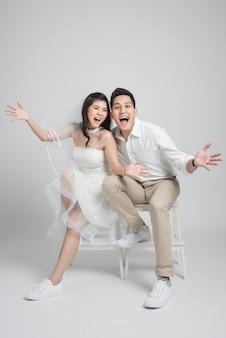 Feliz novia y el novio sentado en una silla