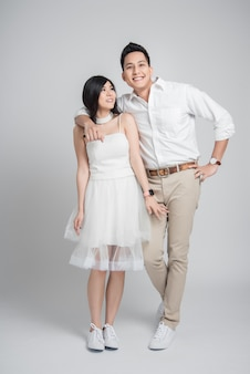 Feliz novio asiático abrazando a su novia en vestido de novia casual