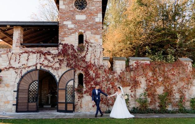 Feliz novio y novia están tomados de la mano juntos y caminando frente al antiguo edificio de piedra en el cálido día de otoño