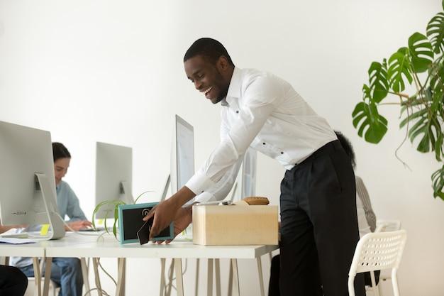 Feliz nuevo empleado africano desempaquetando pertenencias en el primer día laborable