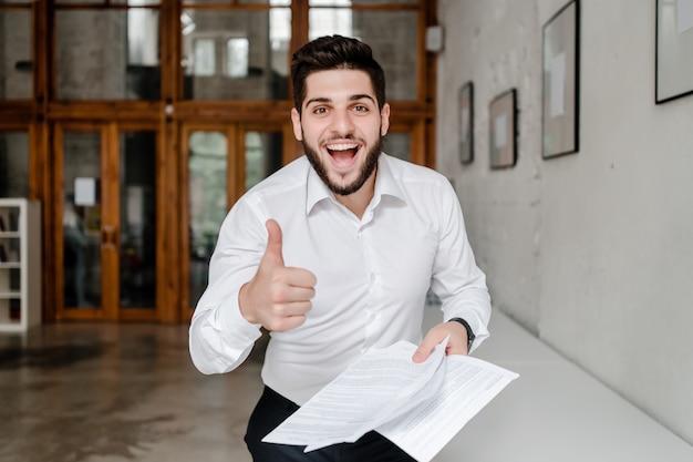Feliz oficinista del medio oriente sonriendo y mostrando los pulgares para arriba