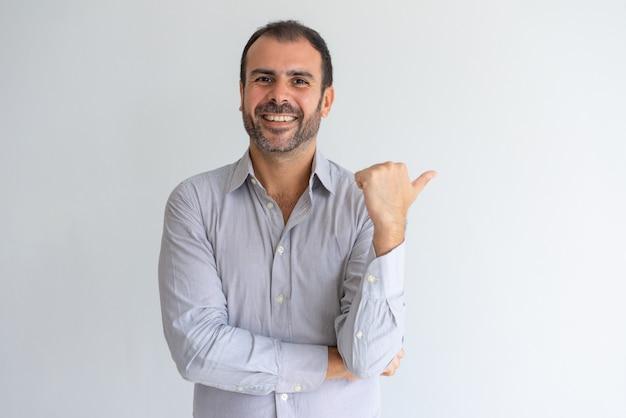 Feliz optimista guapo gerente de ventas latina apuntando a un lado y mirando a cámara.