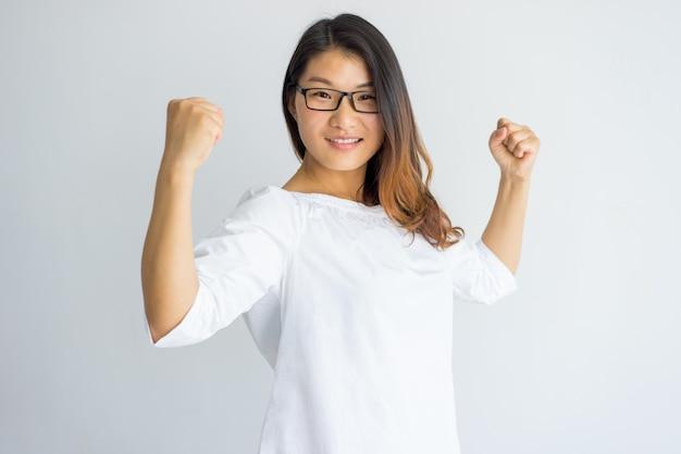 Feliz optimista joven mujer asiática en anteojos mostrando su poder