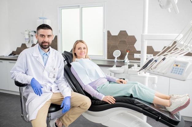 Feliz paciente rubia y joven dentista exitoso en bata blanca y guantes sentado en la oficina de odontología de las clínicas contemporáneas