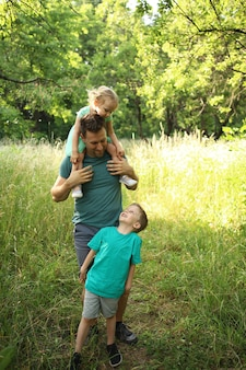 Feliz padre amoroso y dos hijos, hijo e hija jugando y abrazándose