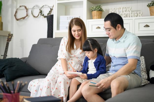 Feliz padre asiático enseñando a su pequeña hija linda a hacer la tarea y dibujar juntos en casa.