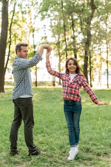 Feliz padre e hija bailando en el jardín