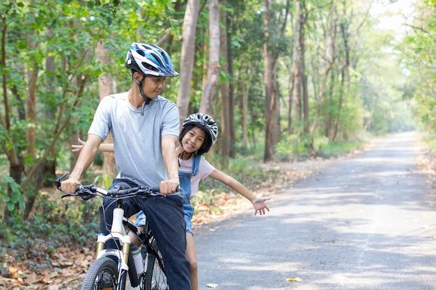 Feliz padre e hija en bicicleta en el parque
