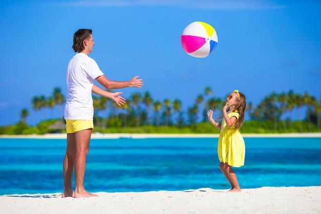 Feliz padre e hija corriendo en la playa con pelota divirtiéndose juntos