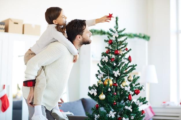 Feliz padre e hija decorando el árbol de navidad