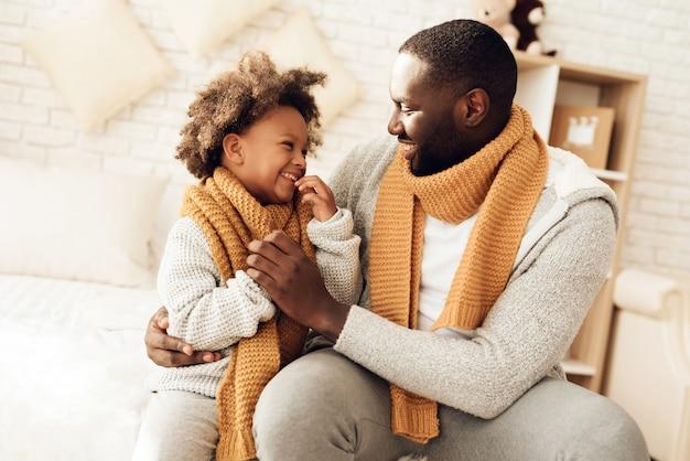 Feliz padre e hija estadounidense sonriendo sentado en la cama.