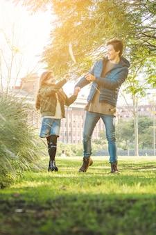 Feliz padre e hija jugando con caña en el parque