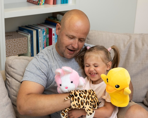 Feliz padre e hija jugando con títeres