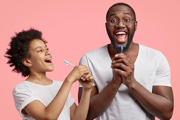 Feliz padre e hijo alegres de piel oscura sostienen toothbrsuh y afeitadora, tienen rutina matutina juntos
