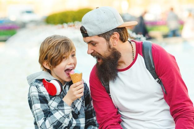 Feliz padre e hijo comiendo helado al aire libre. familia feliz en un paseo.