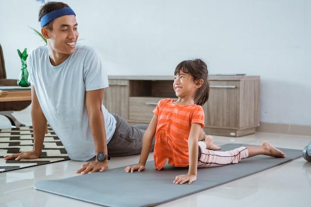 Feliz padre e hijo haciendo deporte juntos. retrato de familia sana e hija estiramientos de entrenamiento en casa