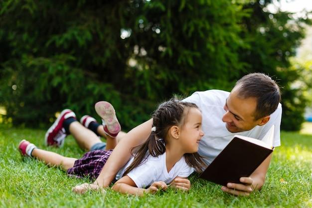 Feliz padre e hijo leyendo un libro en la naturaleza