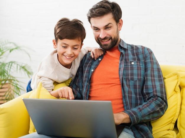 Feliz padre e hijo mirando en la computadora portátil