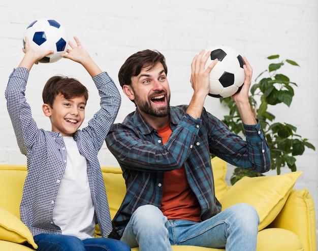 Feliz padre e hijo sosteniendo balones de fútbol