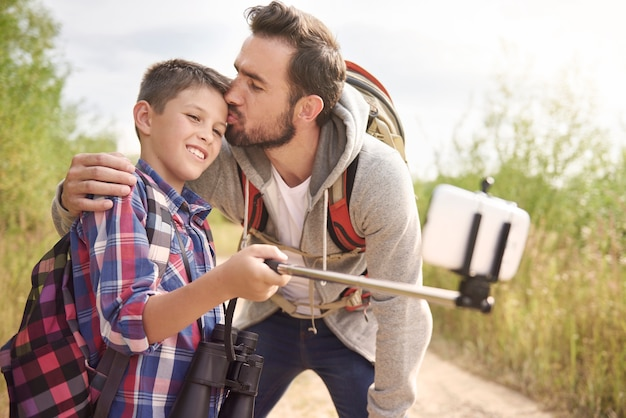 Feliz padre e hijo tomando selfie durante el senderismo