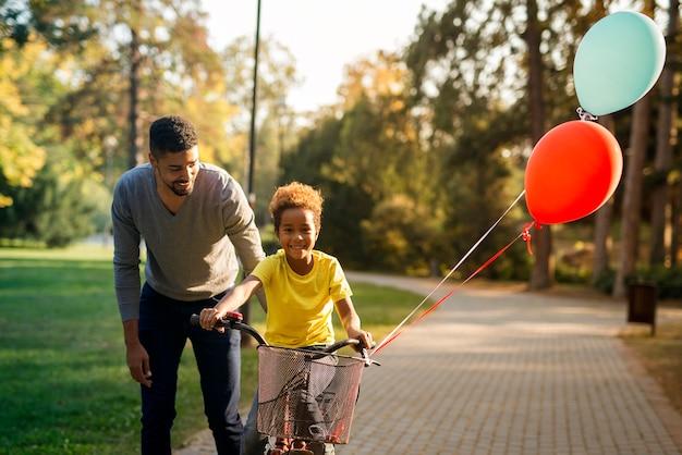 Feliz padre enseñando a su linda hija a andar en bicicleta en el parque