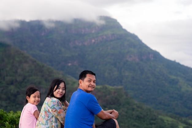 Feliz padre de familia asiática, madre e hija sentadas en la cima de la hermosa montaña sosteniendo las manos levantadas