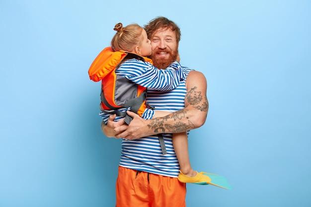Feliz padre feliz de recibir cariñosos besos y abrazos de su hija, la sostiene en las manos, vestida con jerséis de marinero, la niña usa chaleco salvavidas naranja y aletas, pasar las vacaciones de verano juntos, divertirse