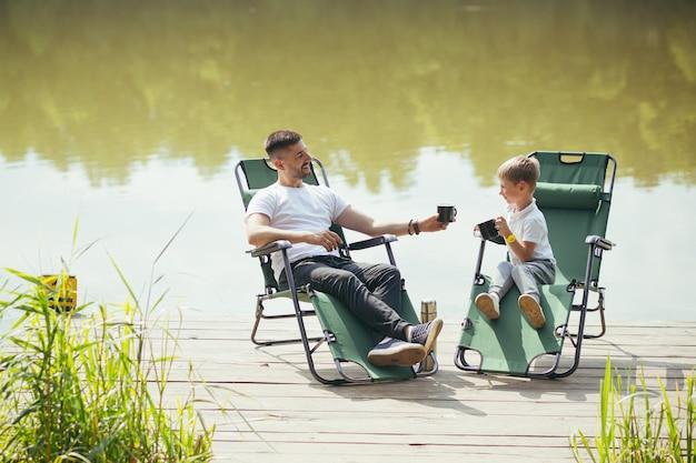 Feliz padre con hijo pequeño descansando junto al lago sentados en cómodas sillas en un muelle de madera. papá y niño pasan tiempo libre juntos al aire libre. vacaciones de campamento en el campo. dia del padre