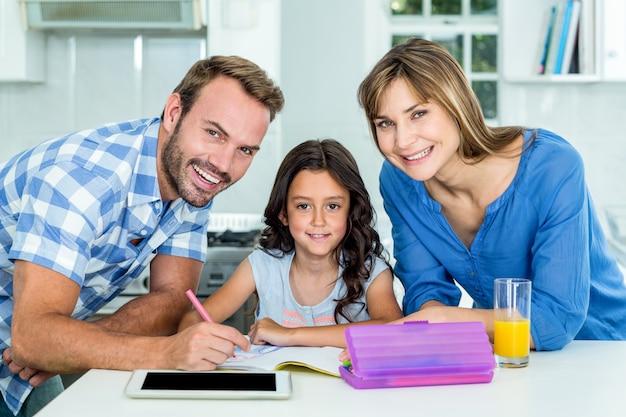 Feliz padre y madre ayudando a la hija en la tarea en casa