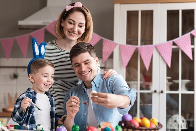 Feliz padre y madre pintando huevos con niño
