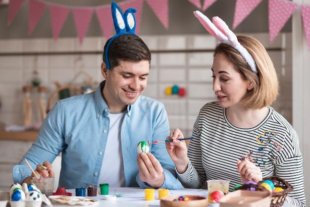 Feliz padre y madre pintando huevos de pascua